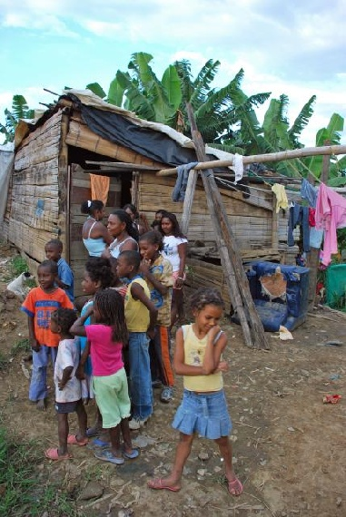 Families outside in squalid surroundings of Agua Blanca near Cali, Colombia
